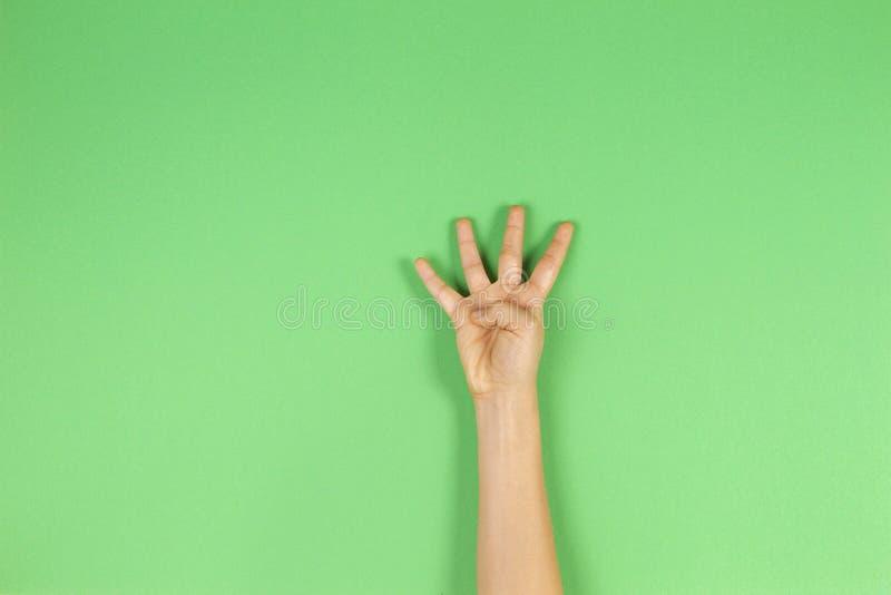 Mano del niño que muestra cuatro fingeres en fondo verde imagenes de archivo