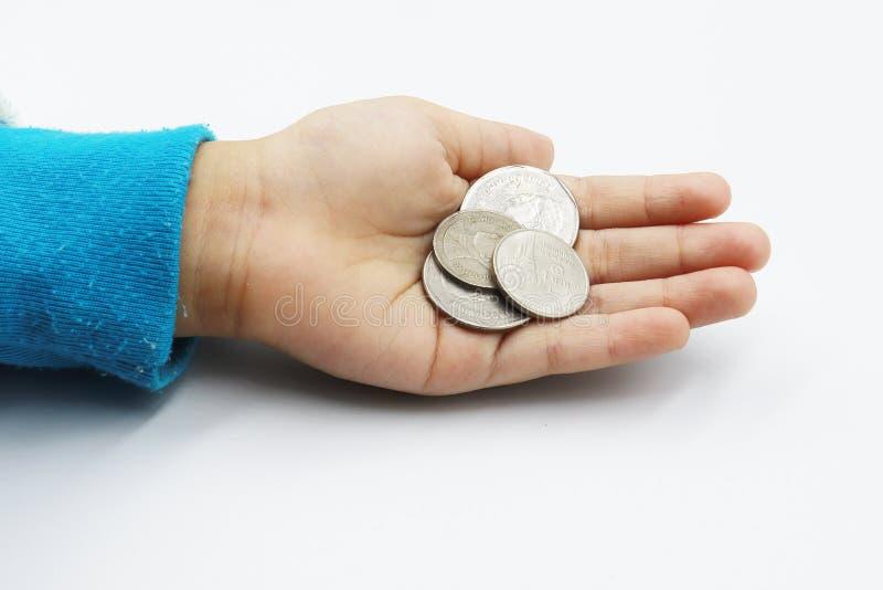 Mano del niño que muestra las monedas del dinero, niño sosteniendo monedas en su aislante de la mano en el fondo blanco fotos de archivo libres de regalías