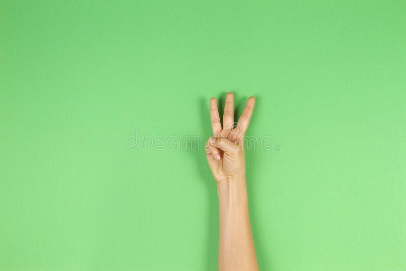 Mano del niño que muestra tres fingeres en fondo verde imagen de archivo libre de regalías