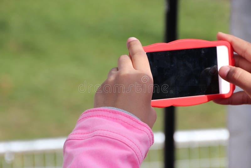 Mano del niño que sostiene la pequeños cámara/teléfono imagenes de archivo