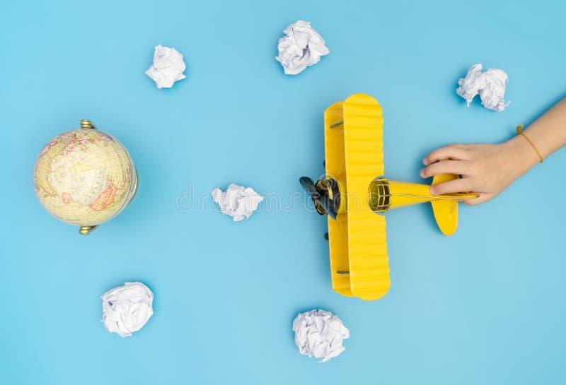 Mano del niño que tira del avión en el cielo para el viaje del globo de la tierra imágenes de archivo libres de regalías