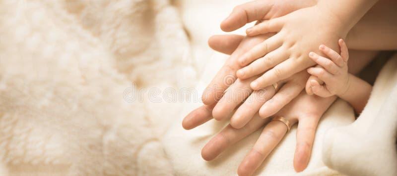 Mano del niño recién nacido Primer de la mano del bebé en las manos de los padres Concepto de la familia, de la maternidad y del  imagen de archivo libre de regalías