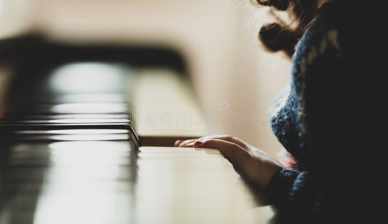 Mano del ni?o de la muchacha que juega el piano imagen de archivo libre de regalías