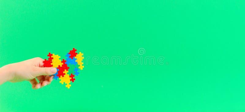 Mano del ni?o que lleva a cabo el coraz?n colorido en fondo verde Concepto del d?a de la conciencia del autismo del mundo imagen de archivo