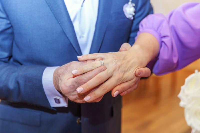 Mano del novio que pone el anillo de bodas en el finger de la novia fotos de archivo