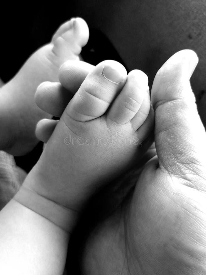 Mano del padre que lleva a cabo pies del bebé imagenes de archivo