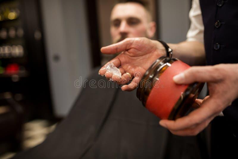 Mano del peluquero con el gel de pelo fotos de archivo
