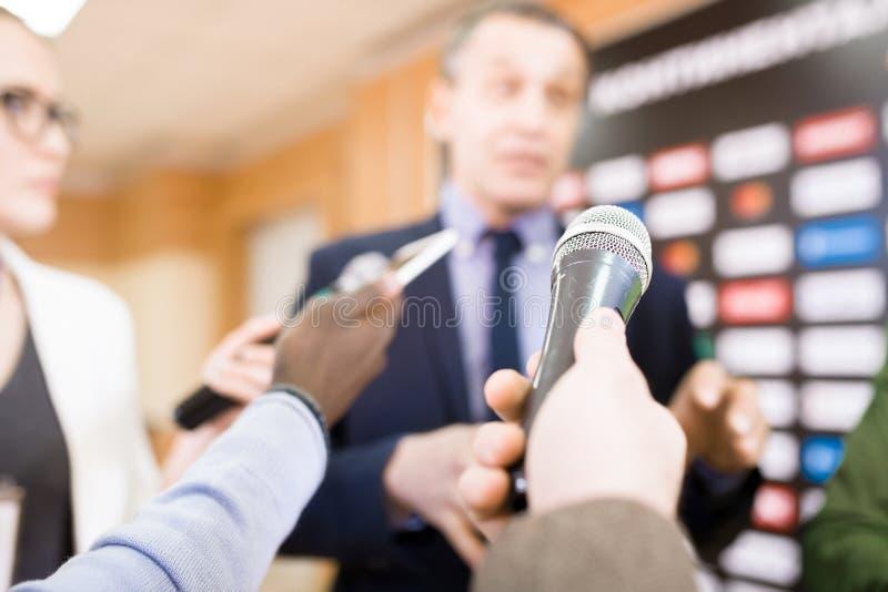 Mano del periodista con el micrófono fotos de archivo