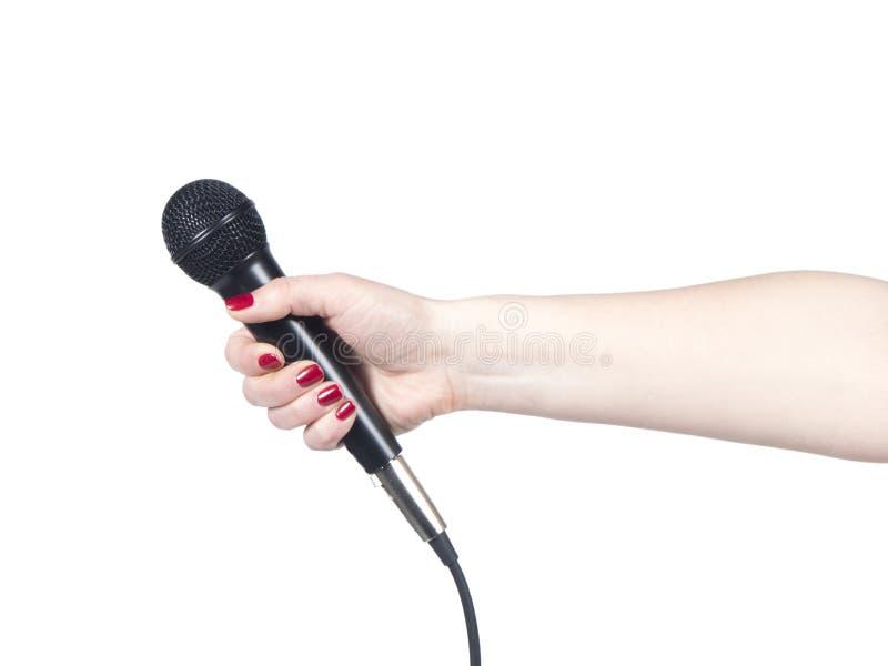Mano del periodista que sostiene el micrófono en el fondo blanco imagenes de archivo