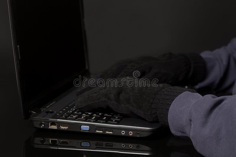 Mano del pirata informático en el guante que trabaja en el ordenador portátil Concepto de cortar criminal de Internet imágenes de archivo libres de regalías