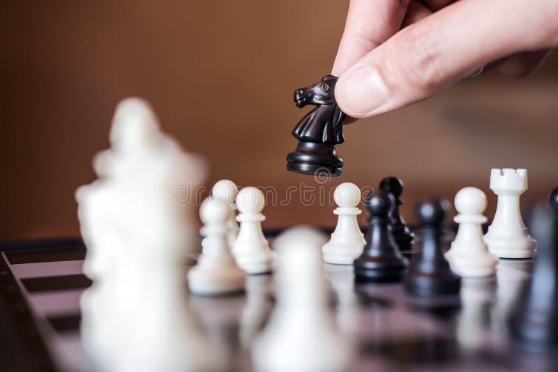 Mano del playin confiado del negro del pedazo de ajedrez del caballo del uso del hombre de negocios fotos de archivo