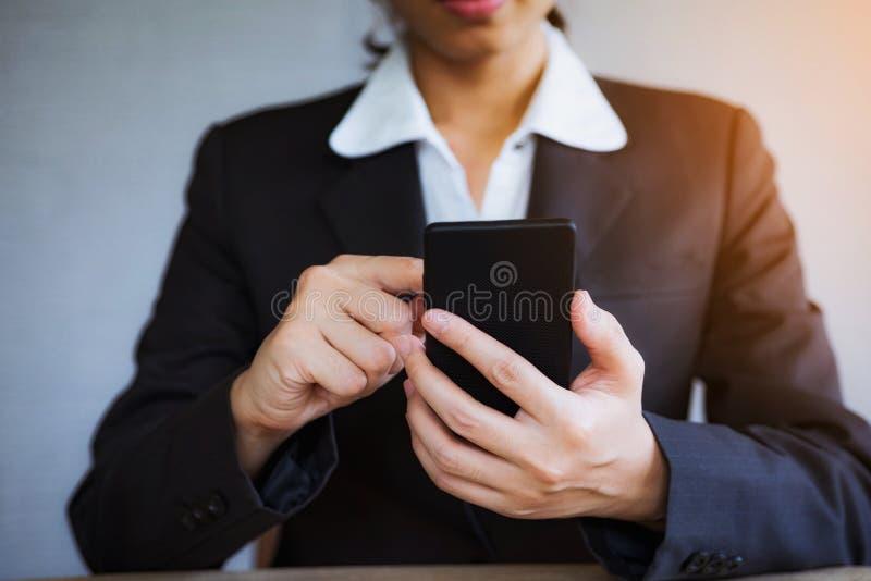 Mano del primer de la mujer de negocios usando el teléfono móvil elegante en la oficina fotografía de archivo