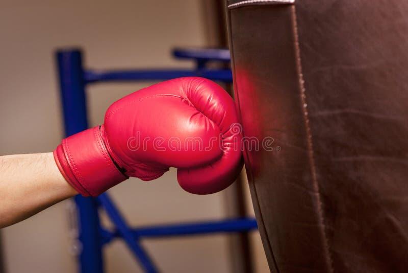 Mano del primer del boxeador en el momento del impacto en el saco de arena imagenes de archivo