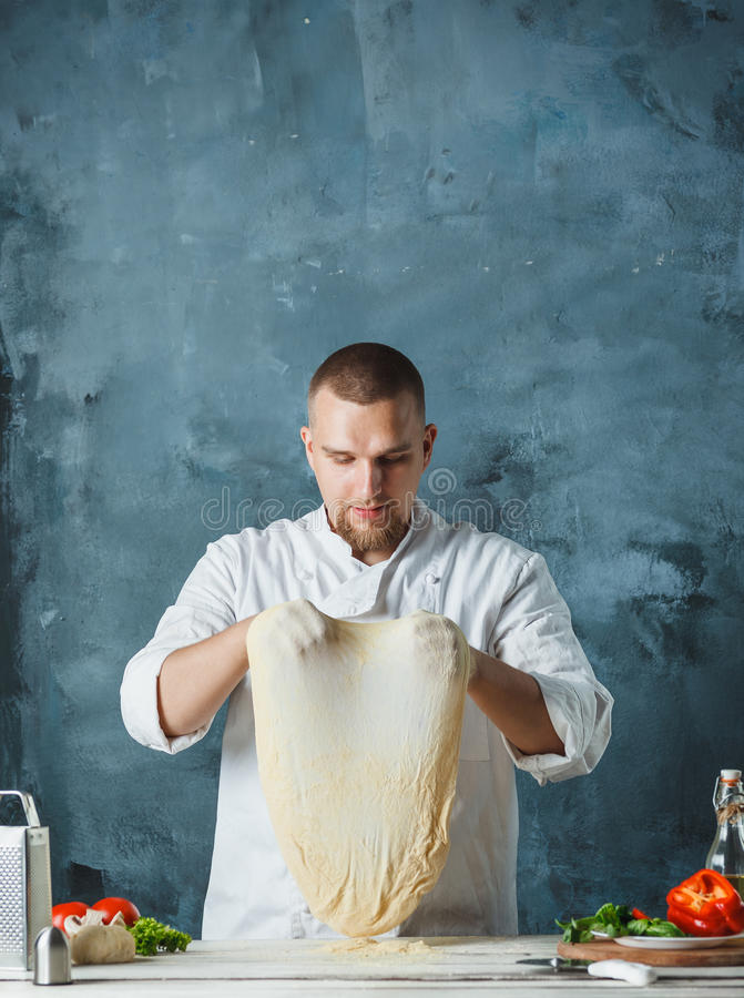 Mano del primo piano del panettiere del cuoco unico in pizza di fabbricazione uniforme di bianco alla cucina fotografia stock libera da diritti
