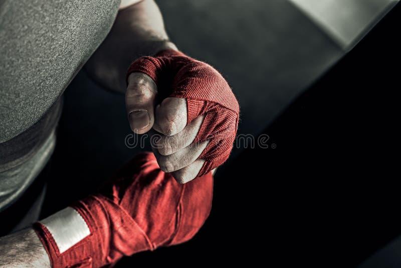 Mano del primo piano del pugile con le fasciature rosse fotografie stock libere da diritti
