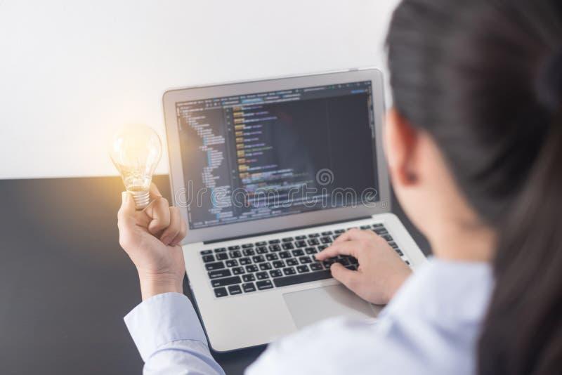 Mano del programador de la mujer joven que sostiene la bombilla, manos de la mujer que cifran y que programan en el ordenador por fotos de archivo libres de regalías