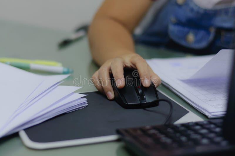 Mano del ratón del uso de la trabajadora en trabajo foto de archivo