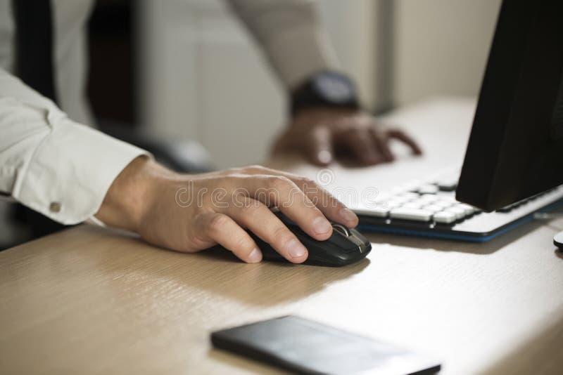 Mano del ratón y de mecanografiar del ordenador del uso del hombre de negocios, sociedad a foto de archivo libre de regalías