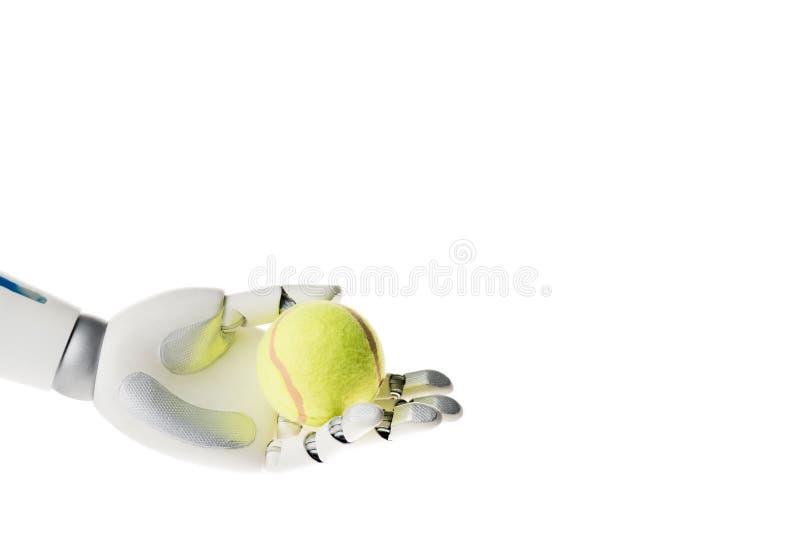 mano del robot che tiene pallina da tennis gialla fotografie stock