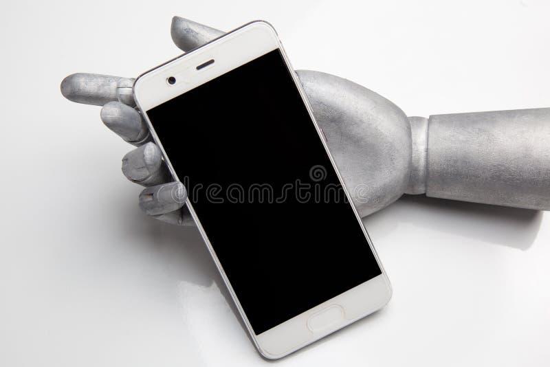 Mano del robot que sostiene el teléfono móvil de la pantalla negra en blanco foto de archivo