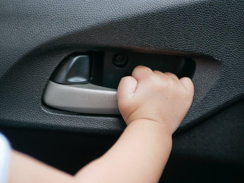 Mano del ` s del bebé alrededor para tirar del tirador de puerta desde adentro de un coche móvil imagen de archivo