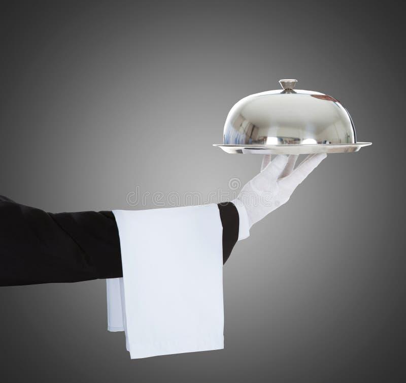 Mano del ` s del camarero que sostiene la campana de cristal y la bandeja imágenes de archivo libres de regalías
