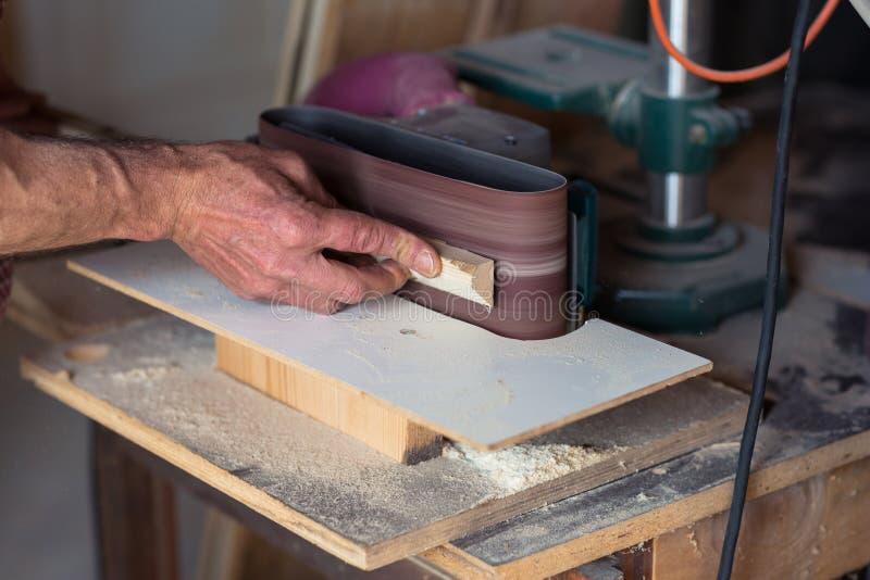 Mano del ` s del carpentiere facendo uso dello strumento della sabbiatrice elettrica fotografia stock