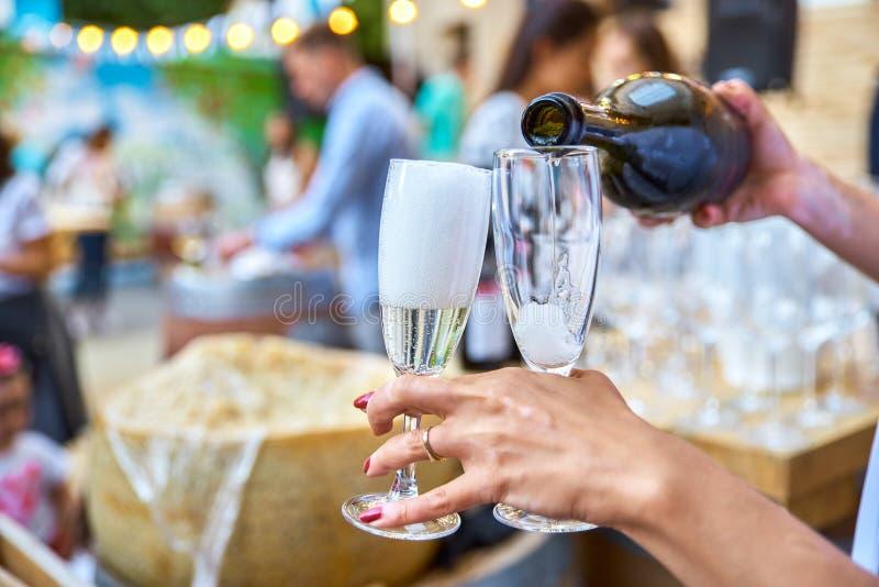 Mano del ` s de la mujer con dos vidrios de champán Los vierte champa imagenes de archivo