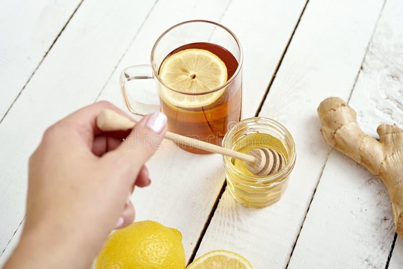 Mano del ` s de la mujer con un palillo para la miel y un té caliente delicioso con el limón en una tabla de madera foto de archivo