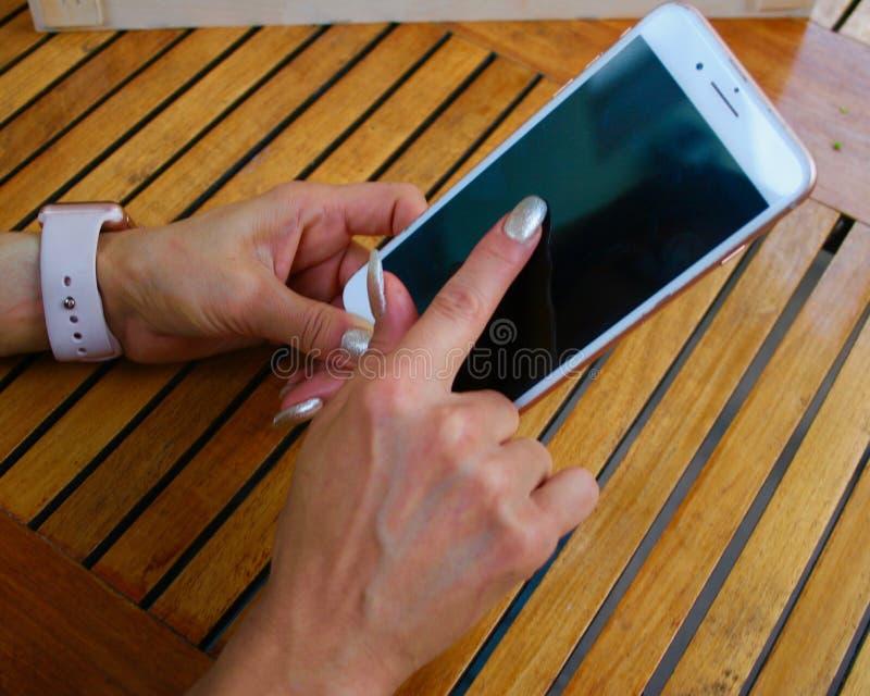 Mano del ` s de la mujer de Latina que sostiene iphone fotografía de archivo