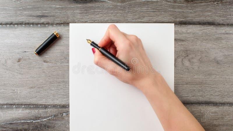 Mano del ` s de la mujer que sostiene la pluma negra lista para escribir en espacio en blanco imagenes de archivo