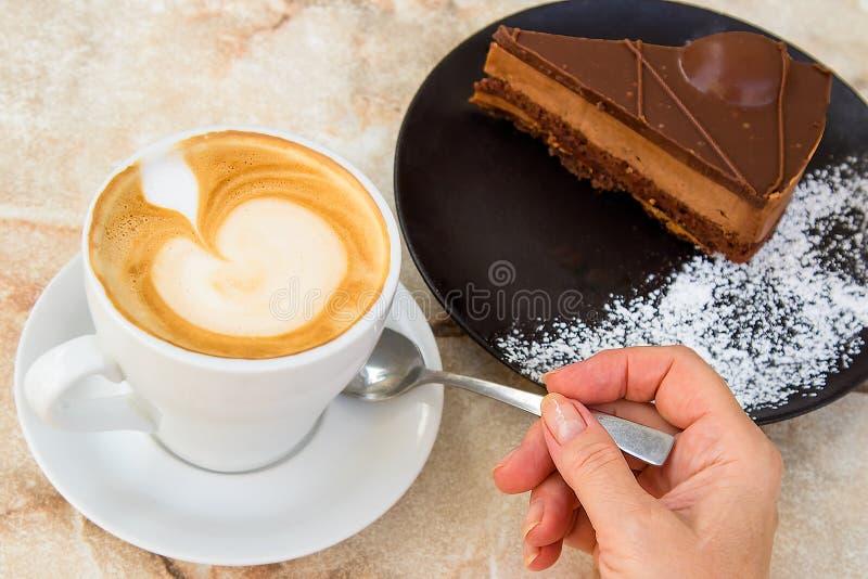 Mano del ` s de la mujer que sostiene una cucharilla y una taza de latte y de placa del café con el pedazo de torta imagen de archivo libre de regalías