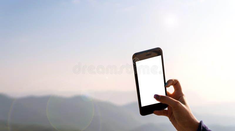 Mano del ` s de la mujer que toma imágenes de la naturaleza con los teléfonos móviles foto de archivo libre de regalías
