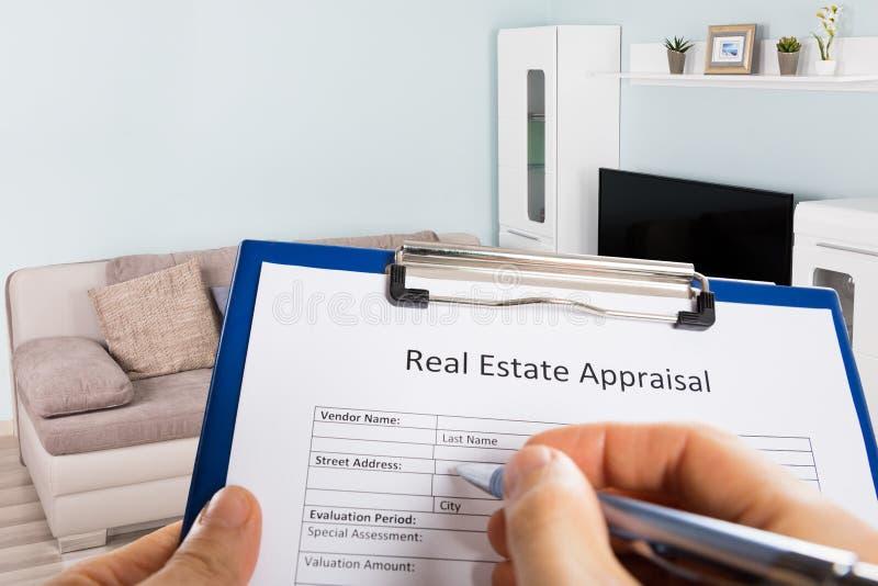 Mano del ` s de la persona que rellena el impreso de la valoración de Real Estate imagen de archivo
