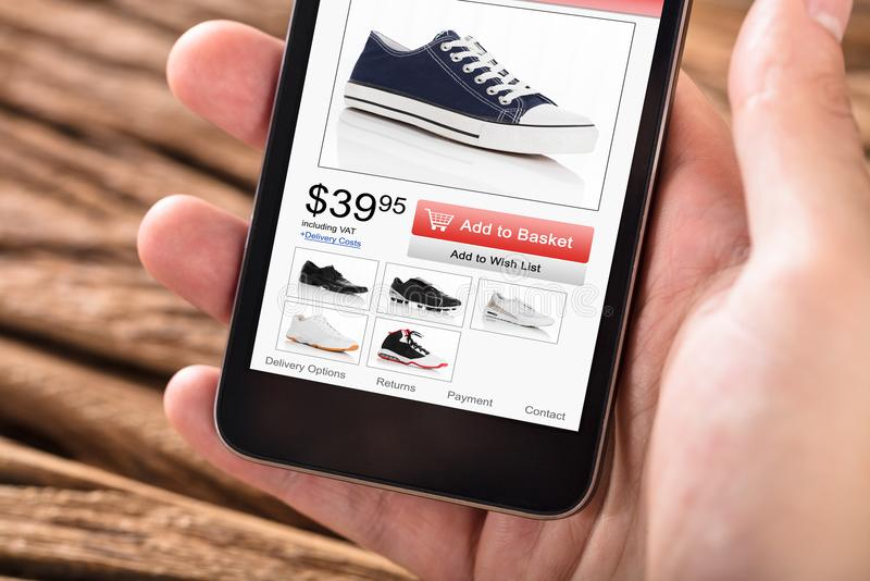 Mano del ` s de la persona que sostiene el teléfono móvil con sitio web de las compras imagen de archivo libre de regalías