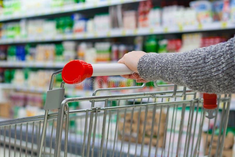 Mano del ` s de las mujeres en la carretilla en supermercado fotografía de archivo