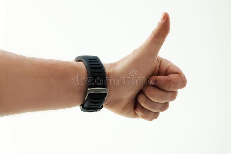 Mano del ` s de los hombres con el reloj elegante en el fondo blanco Pulgares para arriba éxito Emoción humana foto de archivo