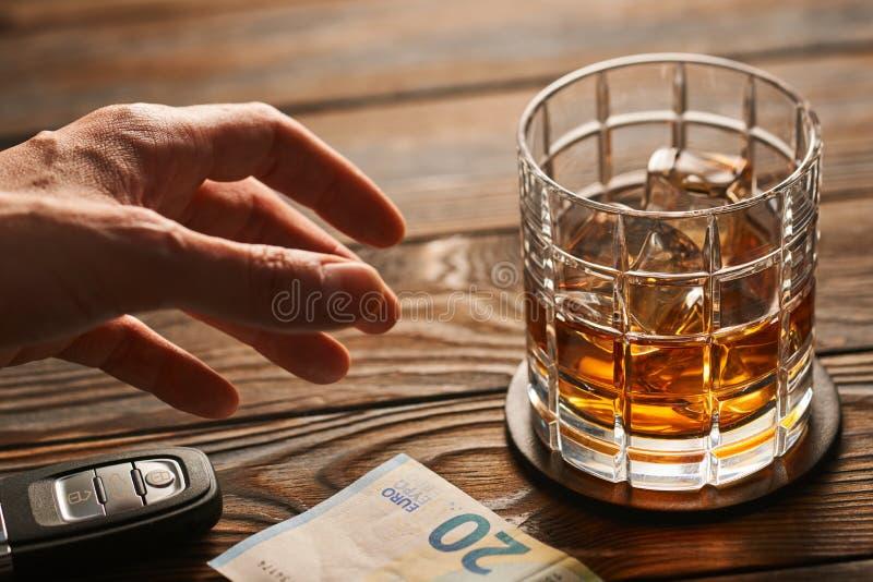 Mano del ` s del hombre que alcanza al vidrio con la bebida del alcohol y la llave del coche Concepto de la bebida y de la impuls imágenes de archivo libres de regalías