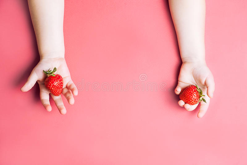 Mano del ` s del niño que sostiene la fresa en el fondo rosado, placa de fresas Concepto sano de la consumición Visión superior,  fotos de archivo libres de regalías
