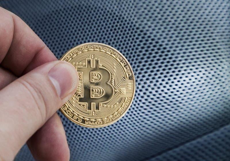 Mano del ` s dell'uomo che tiene Bitcoin dorato immagini stock libere da diritti