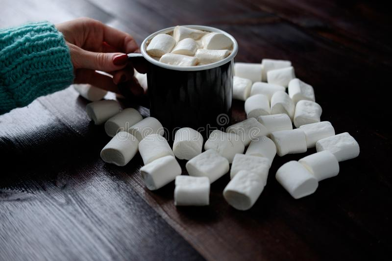 Mano del ` s della donna che tiene tazza di caffè nera con le caramelle gommosa e molle fra fotografie stock