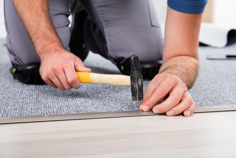 Mano del ` s della persona facendo uso del martello e del chiodo fotografia stock