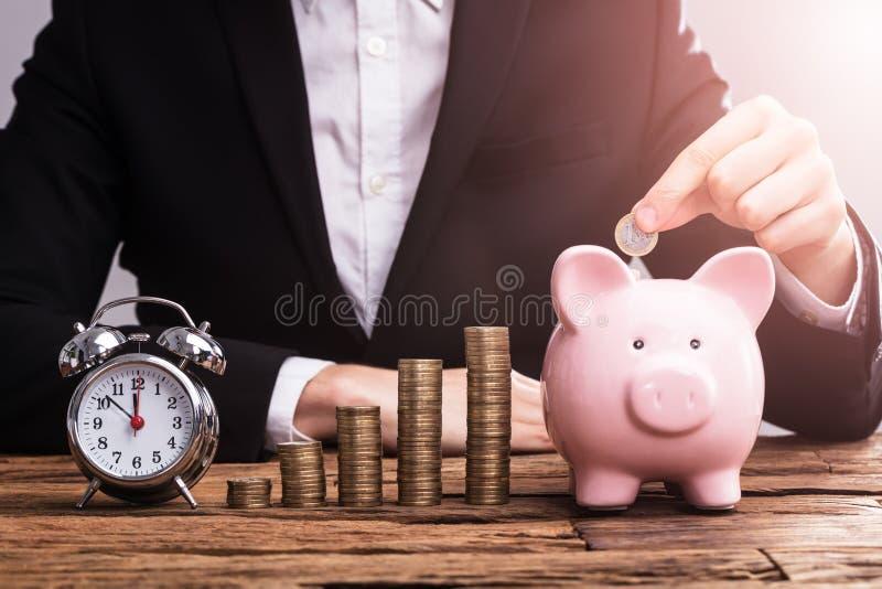Mano del ` s del empresario que pone la moneda en Piggybank imagen de archivo