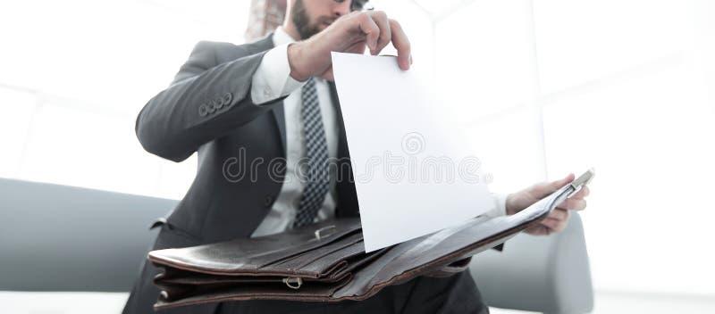 Mano del ` s del hombre de negocios con suitecase en una oficina moderna foto de archivo libre de regalías