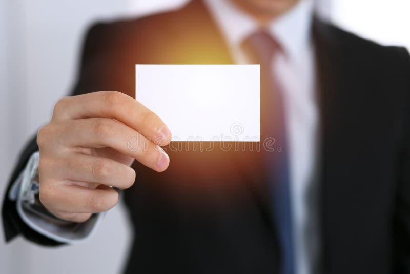 Mano del ` s del hombre de negocios que sostiene la tarjeta de visita con el espacio vacío, primer fotografía de archivo libre de regalías