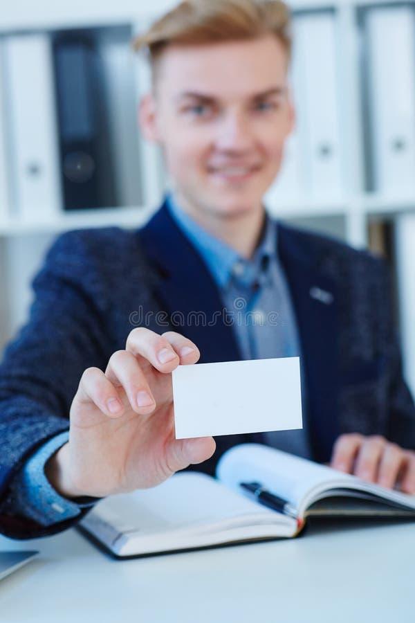 Mano del ` s del hombre de negocios que sostiene la tarjeta de visita en blanco Mano masculina que muestra el primer blanco de la imagen de archivo