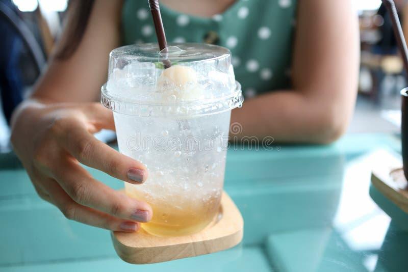 Mano del succo del litchi della tenuta della donna di Yong con soda fotografia stock