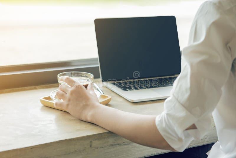 Mano del tacto de la mujer en la taza de café sólo caliente mientras que usa el ordenador portátil Comercio electrónico, educació imagen de archivo libre de regalías