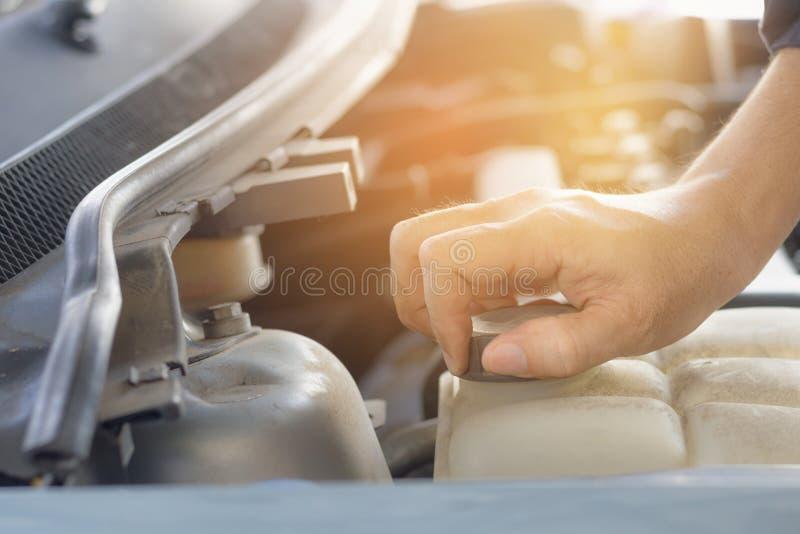 Mano del tanque de agua abierto del casquillo del hombre de coche para el mantenimiento fotos de archivo