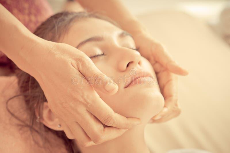 Mano del terapista che massaggia su un fronte della donna in stazione termale immagine stock